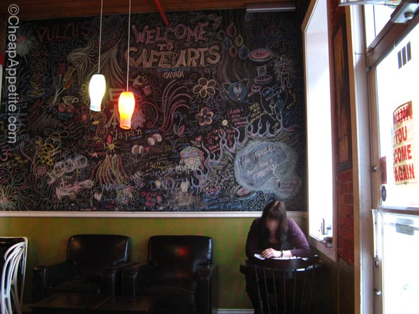 Cozy corner at Cafe Des Arts featuring a lovely blackboard chalk art